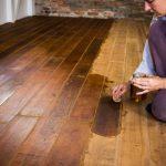 Kvinna behandlar gammalt trägolv med olja